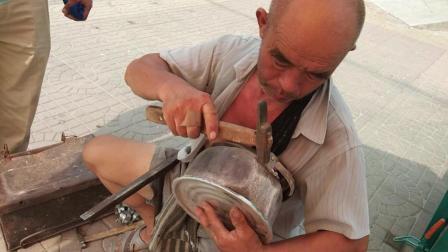 烈日炎炎, 70岁的大爷在马路边上补水壶底, 你见过吗?
