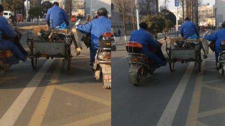 江苏淮安:危险!为帮三轮车运货 两男子骑车助力