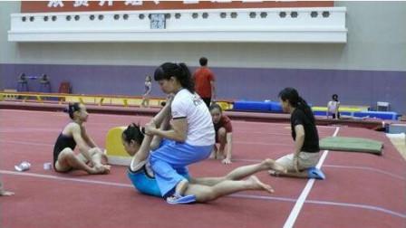 体操教练帮女学员压腿,女孩表情满脸通红,这得有多坚强,看着好心疼