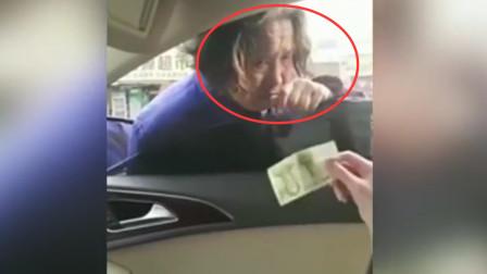 老太太马路中间拦车要钱,女司机好心给1元钱,反被老太砸车辱骂:真抠!