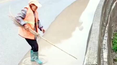 环卫大姐看到桥下面有个水洞,所以拿起棍子就捅开了,环卫大姐真好!