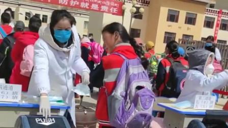 河南孩子进校门口的时刻,老师为她们换上新的口罩