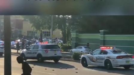 美国街头混乱,一女子用石头砸警车,周围有市民欢呼