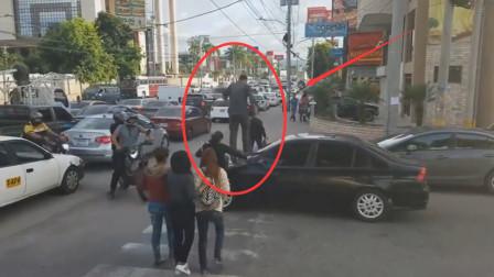 小车停在斑马线上,众人过马路,直接从黑色轿车上踏过去