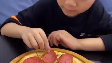 童年的记忆:萌娃戴上手套在吃披萨