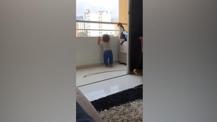 操碎心!1岁小萌娃在阳台抓栏杆玩 猫保姆不顾危险贴身保护孩子