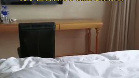 20日,辽宁锦州一男子住酒店给手机充电像在输液。