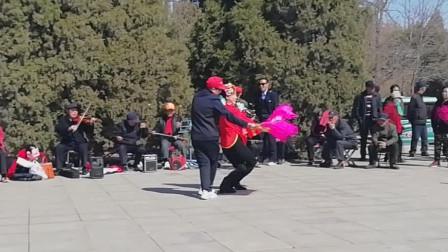 享受明媚春光 公园内两位老人伴乐现唱东北二人转小帽《逛花灯》吸引大量游人