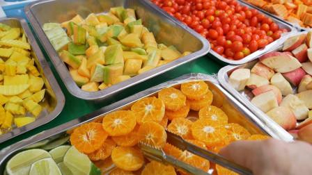 开在学校旁的摊位,食客任意挑选水果,10元一杯,啥也不放只管榨