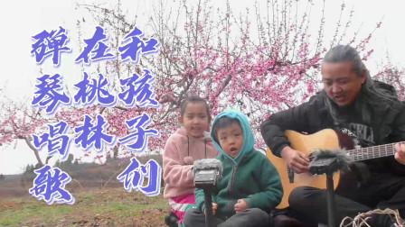 在漫山遍野的桃花树下,和孩子们玩一首吉他弹唱,结果孩子着急了