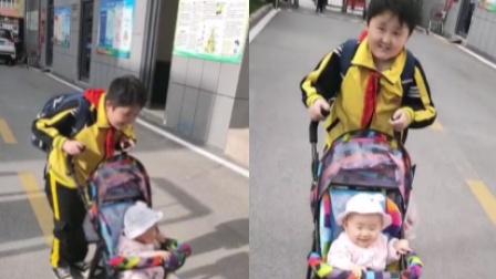 10岁哥哥推着1岁妹妹上街 见到认识人就炫耀