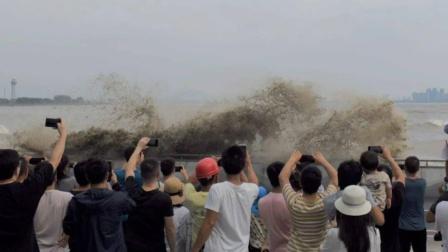 钱塘江大潮突然翻起十几米巨浪 有女游客直接被打懵