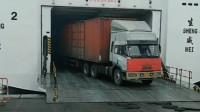 重型卡车拉着两个大集装箱, 以倒车的方式驶上了汽车渡轮
