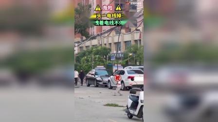 郑州街头一男孩手抓电线摆动